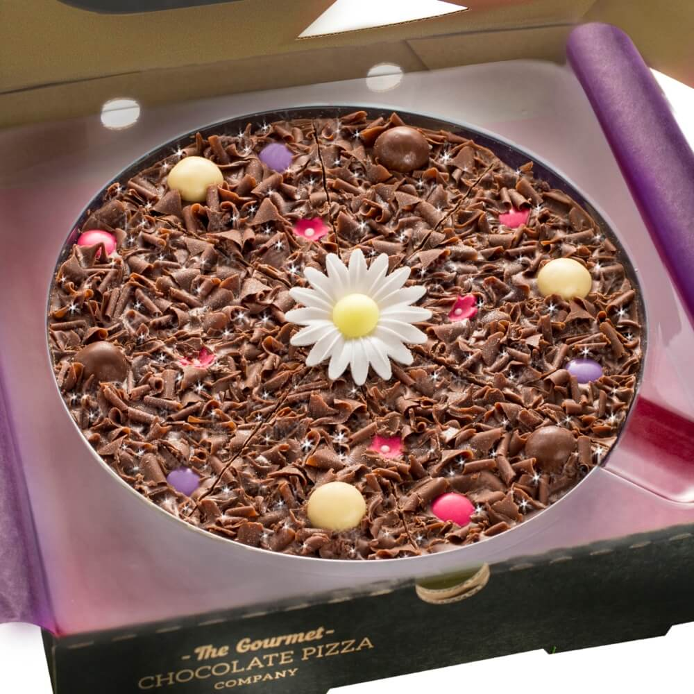 Our Mother's Day Flower Chocolate Pizza sees milk chocolate curls, and pink and purple rainbow chocolate drops nestled on a solid milk chocolate base, with a wafer daisy in the centre.