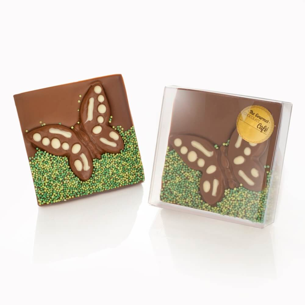 Solid Belgian milk chocolate bars inlaid with a milk chocolate butterfly piped with white chocolate wings and finished with a handful of green 'grass' sprinkles.