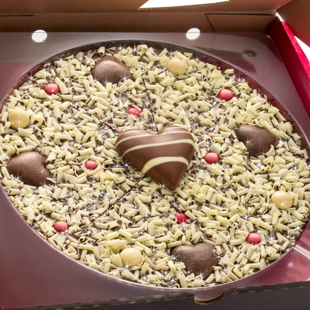 "Close up of our 10"" Valentines Day Chocolate Pizza, with white chocolate curls, white chocolate honeycombed rice balls and red rainbow drops. Finished with four mini milk chocolate hearts and a large solid milk chocolate heart."