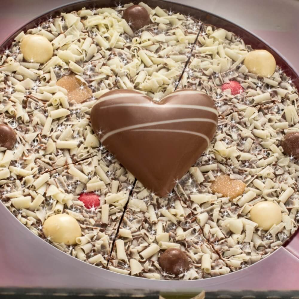 "7"" Valentines Pizza with white chocolate curls, milk chocolate love heart, vanilla fudge and red rainbow drops."